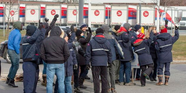 Striking Canada Post workers walk the picket line in front of the Saint-Laurent sorting facility in Montreal on Nov. 15, 2018.