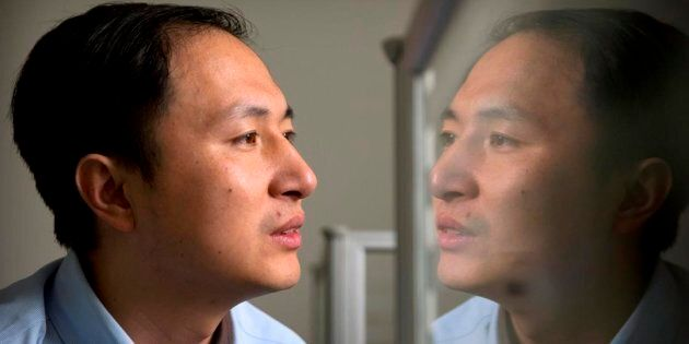 He Jiankui is reflected in a glass panel as he works at a computer at a laboratory in Shenzhen in southern...