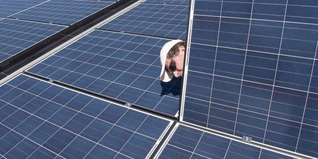 Jason Andriulaitis checks a connection under a new solar panel installation in Scugog, Ont. on April...