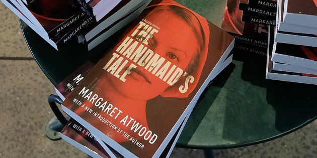 Organizers arrange copies of Margaret Atwood's book 'The Handmaid's Tale' during the Interactive 'The Handmaid's Tale' Art Installation Opening at The High Line on April 26, 2017 in New York City.