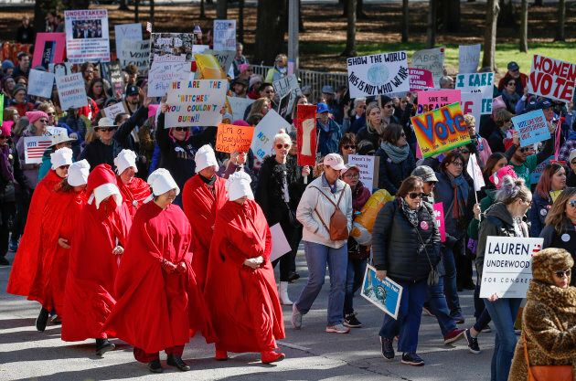 """Women angered by the bitter fight over a US Supreme Court nominee and what they called the 'anti-woman agenda' of the Trump administration headed into the streets of Chicago on Saturday in a display of political might. Dressing in the iconic red """"handmaid's"""" outfit has become a recognizable protest of the treatment of women."""