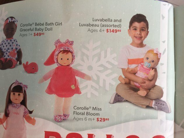 """A little boy holds a baby doll in Indigo's """"What Kinds Want"""" holiday catalogue."""