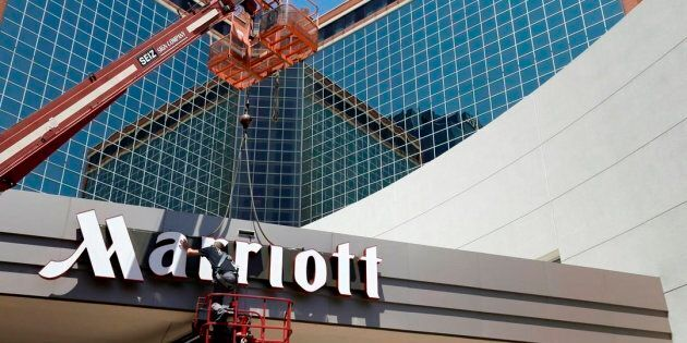 In this Tuesday, April 30, 2013, file photo, a man works on a new Marriott sign in front of the former...
