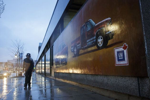 A pedestrian walks past a General Motors mural in downtown Oshawa, Ont. on Monday, Nov. 26,