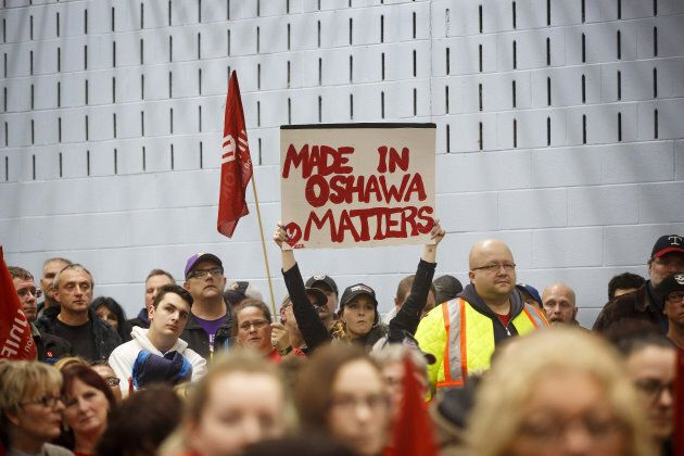 A General Motors worker holds a sign reading 'Made In Oshawa Matters' during an information meeting at...
