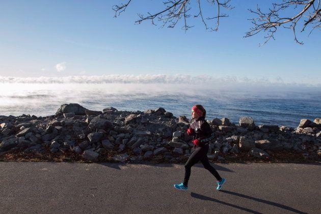 A woman runs beside Lake Ontario in Kingston, Ont. on Nov. 22,