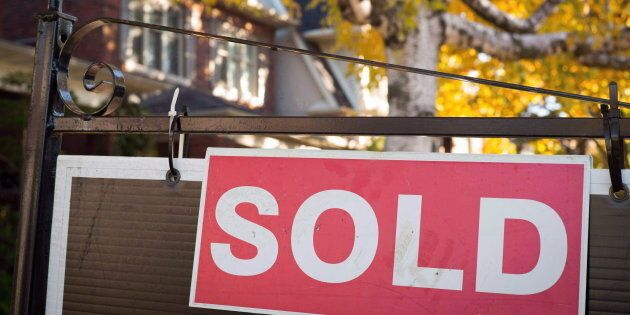 A real estate sold sign hangs in front of a west-end Toronto property Nov. 4,