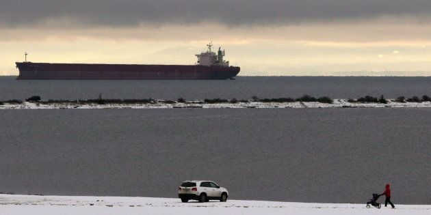 An oil tanker anchors in Strait of Juan de Fuca as a man walks to his car along the grounds of Royal...