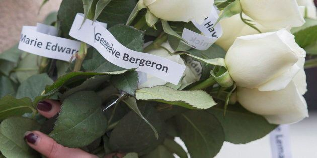 A woman holds white roses adorned with the names of fourteen murdered female students during a ceremony...