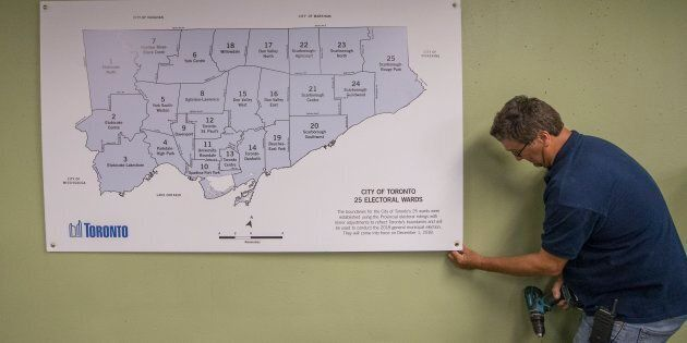 A City employee puts up the map with the 25 council seats on the wall inside the city hall elections...