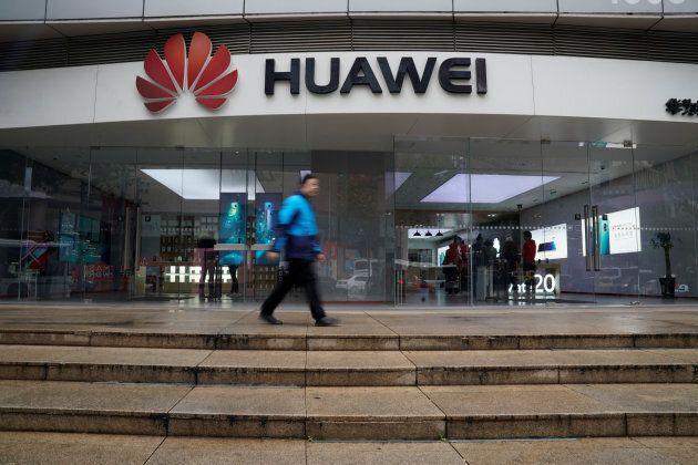 A man walks by a Huawei logo at a shopping mall in Shanghai, China, Dec.