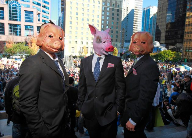 Protesters wear pig masks and business suits as thousands of people participate in the Occupy Vancouver...