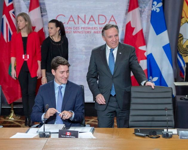 Quebec Premier Francois Legault takes his seat as Prime Minister Justin Trudeau looks on at the start...
