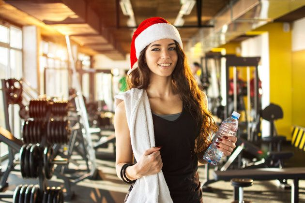 Young woman with red Santa hat, towel and water bottle in gym. Snow effect on