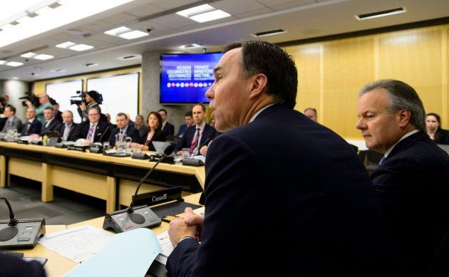 Bank of Canada Governor Stephen Poloz, right, sits at the head of the table as Finance Minister Bill...