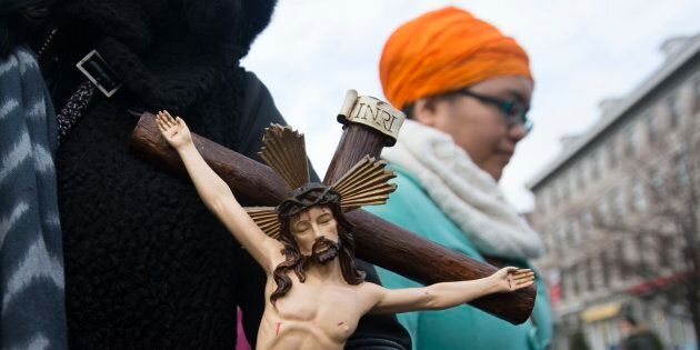 A woman holds a crucifix during a Montreal gathering, Jan. 12, 2014, to oppose a law that would ban the wearing of religious symbols and clothing in all public institutions. A similar law is proposed now by the current provincial government there.