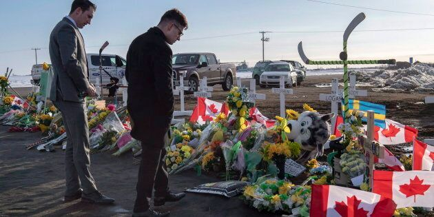 A group of Saskatchewan Junior Hockey League referees look at a memorial at the intersection of a fatal...