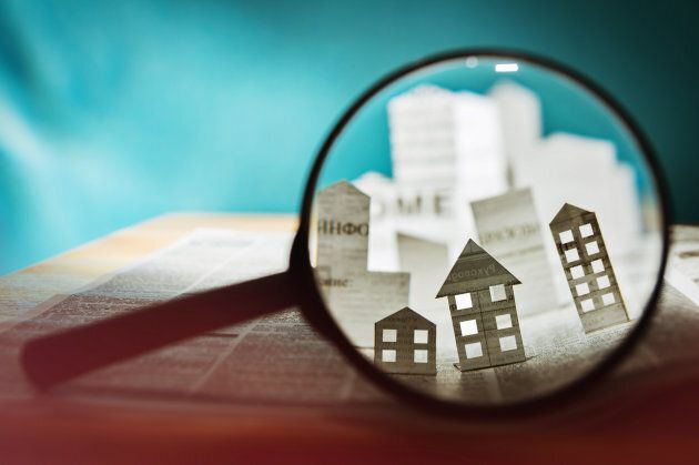 Magnifying glass in front of an open newspaper with paper houses. Concept of rent, search, purchase real