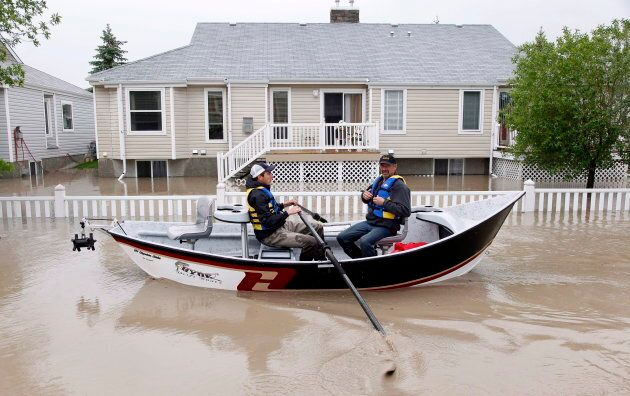 Two men use a fishing boat to rescue residents from a neighborhood after heavy rains caused flooding,...