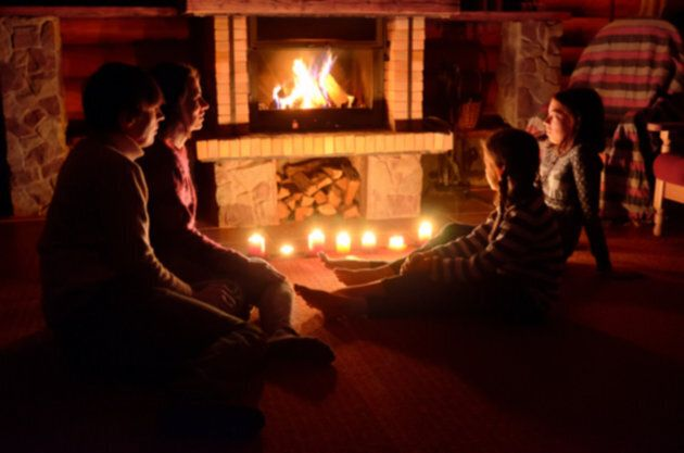 A family relaxing by a fire and candlelight.