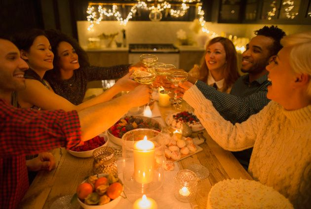 Friends toasting champagne glasses at candlelight table is hygge to the max.