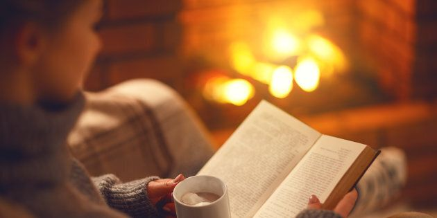 All the elements of hygge encapsulated: blanket, fireplace, tea, book and warm lighting.