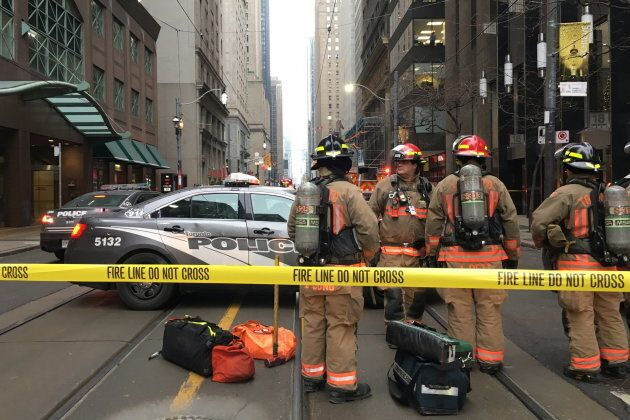 Firefighters stand by their equipment after a bomb threat evacuated the King Street subway station in...