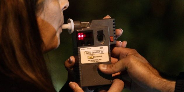 An RCMP officer performs a breathalyzer test on a driver during a roadside check in Surrey, B.C., on...