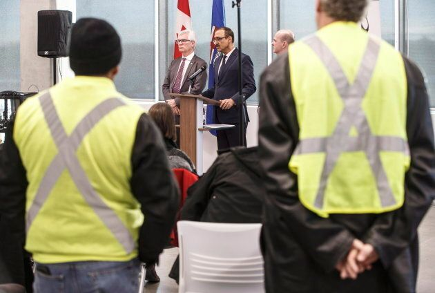Concerned oil field workers watch as Canada's Minister of International Trade Diversification Jim Carr,...