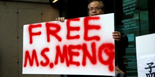 A protester holds a sign outside the B.C. Supreme Court bail hearing of Huawei CFO Meng Wanzhou, Vancouver,...