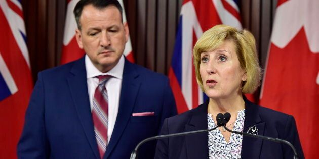 Ontario's Labour Minister Laurie Scott speaks as Energy Minister Greg Rickford looks on during a press...