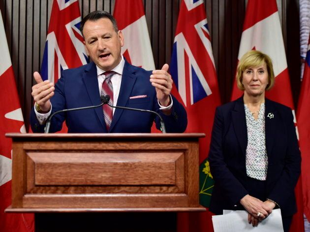 Ontario's Energy Minister Greg Rickford speaks as Labour Minister Laurie Scott looks on during a press...