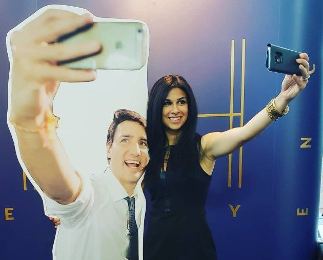 Ontario PC MPP Goldie Ghamari takes a selfie with a cardboard cutout of Prime Minister Justin Trudeau taking a selfie.