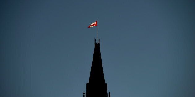 The Canadian Flag is illuminated by morning light atop the Peace Tower on Parliament Hill in Ottawa on...