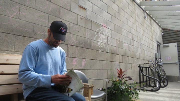 Kevin Drake reading a celebrity magazine.