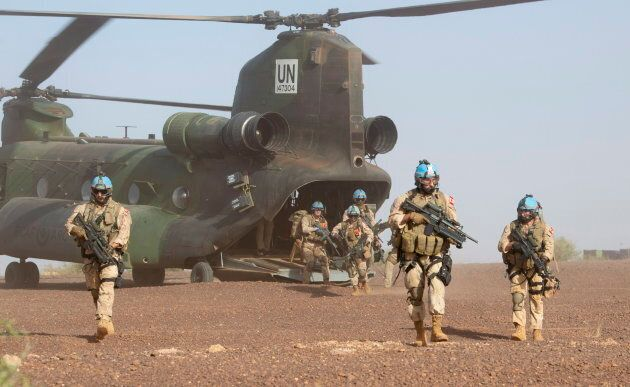 Canadian infantry and medical personnel disembark a Chinook helicopter as they take part in a medical...