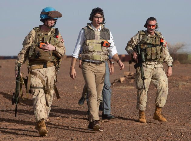 Prime Minister Justin Trudeau, centre, makes his way from a Chinook helicopter to watch a medical evacuation...
