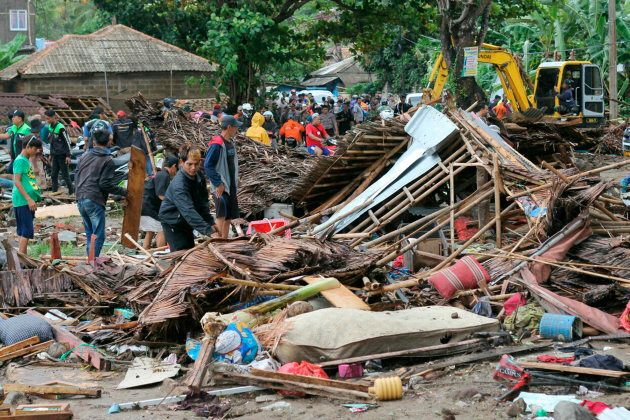 Residents inspect a house damaged by the tsunami, in Carita, Indonesia, Sunday, Dec. 23,