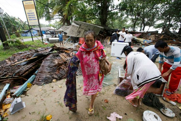 A women inspects her house, which was damaged by a tsunami, in Carita,