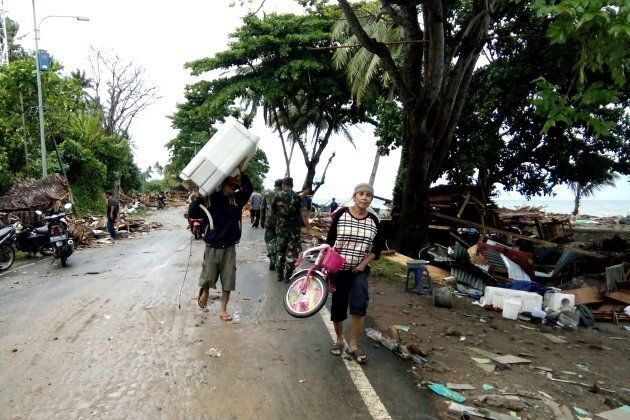 Residents evacuate from damaged homes on Carita beach on December 23,