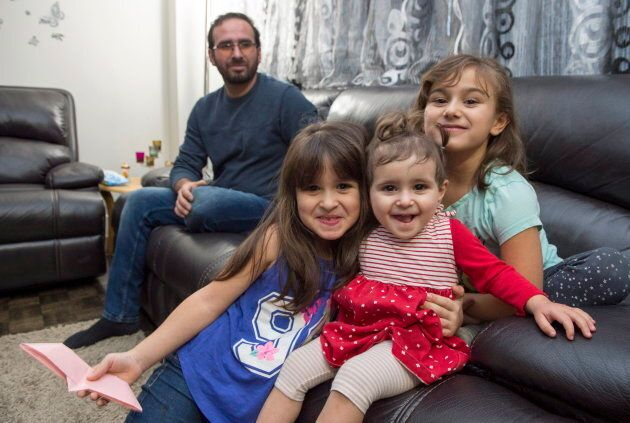 Syrian refugee Mohammad Al Mnajer watches as his three daughters Judy, centre, Jaidaa, left, and Baylasan...