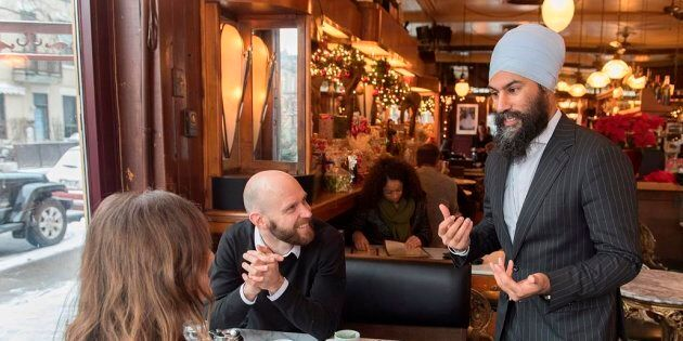 NDP Leader Jagmeet Singh speaks to a man and a woman in a coffee shop during a tour of the Montreal borough...