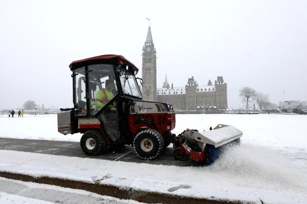 A worker clears a sidewalk as light snow falls on Parliament Hill in on Nov. 20,