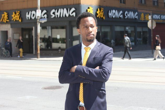 Emile Wickham posing in front of Hong Shing after winning his discrimination case with the Ontario Human Rights Tribunal.