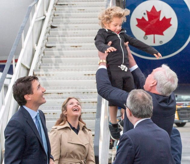 Kevin Vickers, right, tosses Hadrien Trudeau into the air as Prime Minister Justin Trudeau and his wife,...