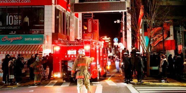 Police and firefighters inspect around the site of a car attack near Takeshita Street in Tokyo, early