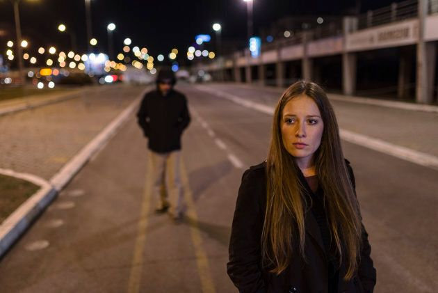 Beautiful young woman walking and being stalked by man criminal on the street at night. Dangerous situation for lonely female. Unrecognizable male figure with hidden face in hood walking, looking dangerous, stalking night robber burglar, bad troubled period, hooded guy Following frightened woman