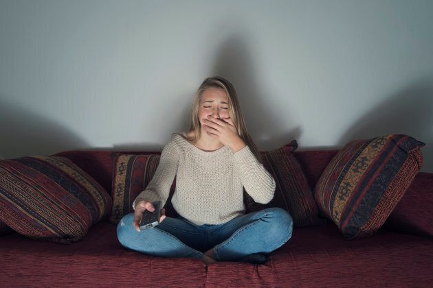 Young woman crying while watching TV