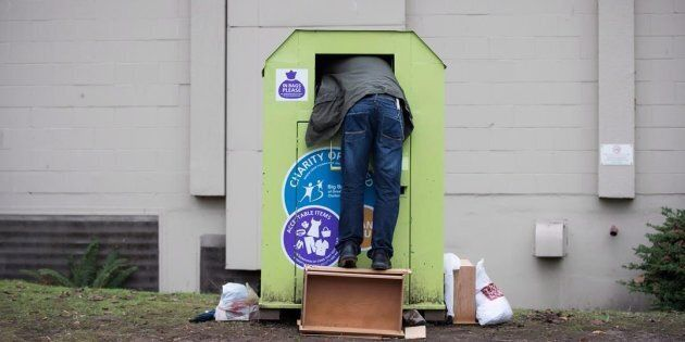 A man tries to retrieve items from a clothing donation bin in Vancouver on Dec. 12,