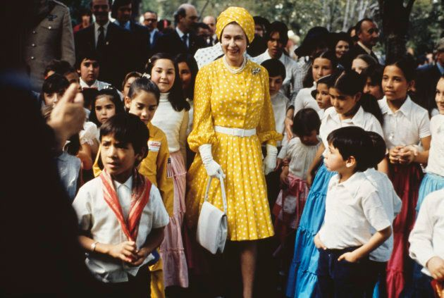 Queen Elizabeth II sporting a turban hat that matches her yellow and white gown, with a group of local...